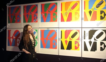 An auction house employee wearing a mask looks at The Book of Love by Robert Indiana, est £60-80,000 at the Preview of Bonhams' Prints & Multiples sale.