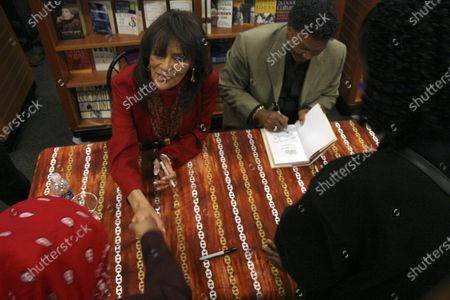 Marilyn McCoo and husband Billy Davis Jr. of the 70's group The 5th Dimension sign copies of their new book Up, Up and Away at the Hue-Man book store in Harlem, NY