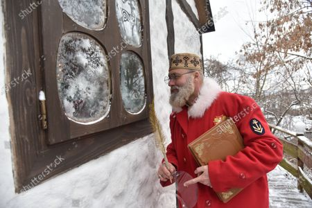 An actor dressed like St. Nicholas looks out the window of the house. The tradition of Saint Nicholas Day is a festival for children in most Orthodox countries in Europe related to surviving legends of Saint Nicholas, and particularly his reputation as a bringer of gifts.