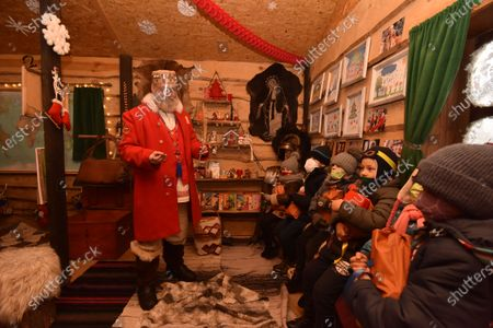An actor dressed like St. Nicholas wearing a face shield as a preventive measure against the spread of covid-19 talks to children. The tradition of Saint Nicholas Day is a festival for children in most Orthodox countries in Europe related to surviving legends of Saint Nicholas, and particularly his reputation as a bringer of gifts.