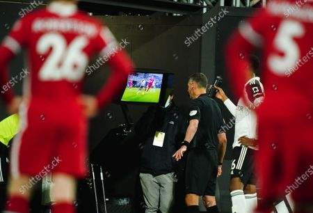 Referee Andre Marriner checks the VAR monitor for a possible penalty to Fulham