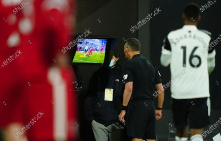 Referee Andre Marriner refers to the VAR monitor before over-ruling his decision to award Fulham a penalty