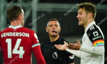 Jordan Henderson of Liverpool and Joachim Andersen of Fulham appear puzzled after referee Andre Marriner gave Fulham a penalty which was overturned after Marriner was asked to refer to the VAR monitor