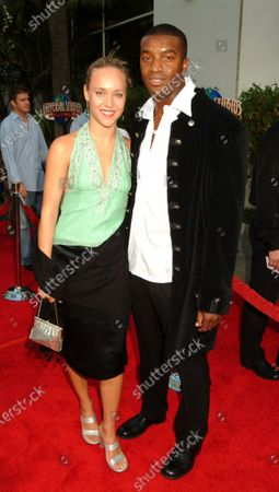 Roger R. Cross with guest on the red carpet of The Chronicles of Riddick-World Premiere, at the Universal City Walk in Los Angeles, CA.