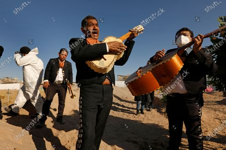 Juarez, Mexico-Dec. 4, 2020-Family and friends gather for the burial of Javier Valdez Martinez, while mariachi music plays at a Juarez cemetery. Javier Valdez, 55, who ran a business loading supplies for border factories, had died of Covid two weeks earlier. A diabetic, he'd been sick for a month. One of his sons also caught the virus, but survived. (Carolyn Cole / Los Angeles Times)