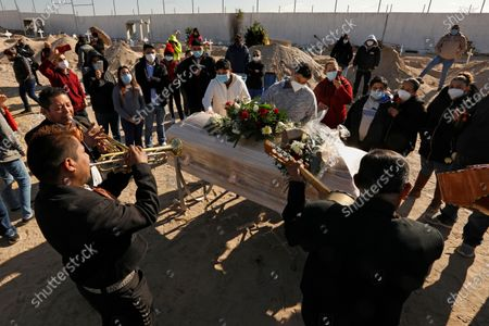 Juarez, Mexico-Dec. 4, 2020-Family and friends gather around the plastic-wrapped casket of Javier Valdez Martinez, while singing to mariachi music at a Juarez cemetery. Javier Valdez, 55, who ran a business loading supplies for border factories, had died of Covid two weeks earlier. A diabetic, he'd been sick for a month. One of his sons also caught the virus, but survived. (Carolyn Cole / Los Angeles Times)