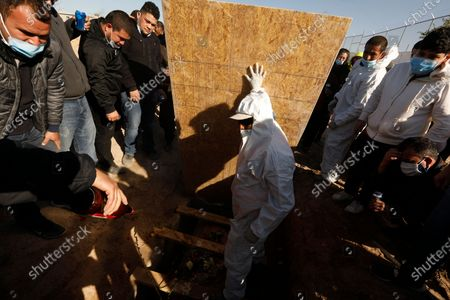Juarez, Mexico-Dec. 4, 2020-Family and friends gather around as the plastic-wrapped casket of Javier Valdez Martinez is lowered into the grave in a Juarez cemetery. Javier Valdez, 55, who ran a business loading supplies for border factories, had died of Covid two weeks earlier. A diabetic, he'd been sick for a month. One of his sons also caught the virus, but survived. (Carolyn Cole / Los Angeles Times)