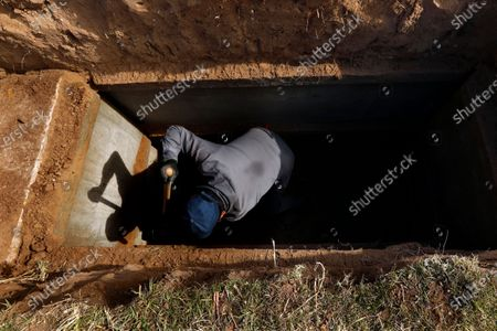 Juarez, Mexico-Dec. 4, 2020-Angel Esparza, 30, started digging graves for Perches at the start of the pandemic when work at the border factory, or maquiladora, slowed. He's wary of the virus; his older brother caught it last month and remains sick. Esparza lives with his 59 year-old diabetic mother, so he wears a mask at work, keeps his distance from mourners, sprays The Covid-19 pandemic has been devastating on the metro area of El Paso, Texas and neighboring Juarez, El Paso. (Carolyn Cole / Los Angeles Times)