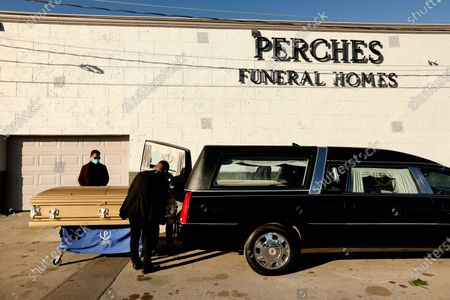 """Stock Picture of Juarez, Mexico-Dec. 4, 2020-Dr. David Gonzalez, far left, stands by as his brother-in-law's casket is moved outside Perches Funeral Home in Juarez, Mexico. Victor Luevano Hidalgo, 46, died of Covid. Gonzalez said, """"We knew it was a risk to come, but my sister couldn't see him for a month. She needed to see him."""" Luevano had been exposed while treating a pregnant patient who arrived in labor and later developed a fever and other Covid symptoms, said Dr. Ruben Mesa, a colleague at the maternity hospital. Mesa blamed Luevano's death on a lack of protective equipment at the hospital, where doctors were only provided one mask per week. Luevano had to buy his own. """"He was very afraid of this, of getting sick,"""" said Gonzalez. """"We're all afraid."""" The Covid-19 pandemic has been devastating on the metro area of El Paso, Texas and neighboring Juarez, El Paso. (Carolyn Cole / Los Angeles Times)"""