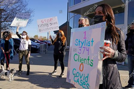 Stock Photo of Hair stylist Marissa Englund, right, holds up a sign during a protest by salon owners and workers against the latest lockdown orders outside the offices of Marin County Health Officer Dr. Matt Willis, in San Rafael, Calif. California health officials are urging the state's residents to stay home as much as possible due to a coronavirus surge taxing the state's hospitals. But the most recent stay-at-home order allows some businesses to remain open, frustrating shuttered business owners who say officials keep sending mixed messages
