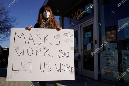 Maya Webb holds up a sign during a protest by hair salon owners and workers against the latest lockdown orders outside the offices of Marin County Health Officer Dr. Matt Willis, in San Rafael, Calif. California health officials are urging the state's residents to stay home as much as possible due to a coronavirus surge taxing the state's hospitals. But the most recent stay-at-home order allows some businesses to remain open, frustrating shuttered business owners who say officials keep sending mixed messages