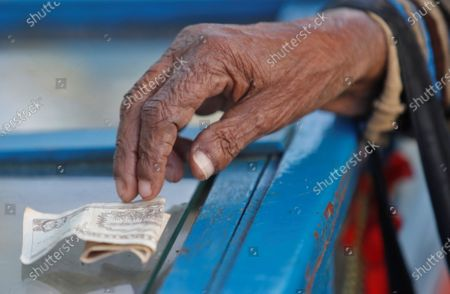 Stock Picture of A customer pays with a Cuban peso bill (CUP) to a candy vendor in Havana, Cuba, 11 December 2020. Cuba will begin its process of monetary and exchange unification on 1 January 2021 with the end of the convertible peso (CUC) - parity with the dollar - which will leave the Cuban peso (CUP) as the only official currency of the country, with a single official conversion rate of 24 pesos per dollar. The long-awaited announcement that puts an end to months of speculation was made on state television by the country's President, Miguel Diaz-Canel.