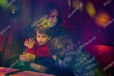 Britain's Kate, Duchess of Cambridge, Prince Louis and Princess Charlotte attend a special pantomime performance at London's Palladium Theatre, hosted by The National Lottery, to thank key workers and their families for their efforts throughout the COVID-19 pandemic