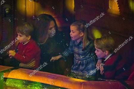 Catherine Duchess of Cambridge with Prince Louis, Princess Charlotte and Prince George attend a special pantomime performance at London's Palladium Theatre, hosted by The National Lottery, to thank key workers and their families for their efforts throughout the pandemic.