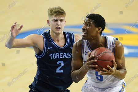 Guard Chris Smith, right, looks for a pass around San Diego guard Joey Calcaterra during an NCAA college basketball game, in Los Angeles