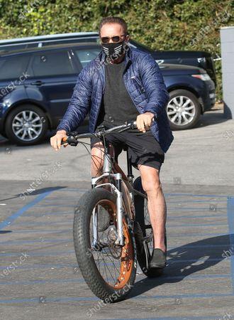 Stock Image of Arnold Schwarzenegger seen on a bike ride in Brentwood