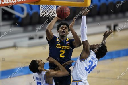 Marquette forward Justin Lewis, center, goes up for a shot against UCLA guard Chris Smith, left, and UCLA guard David Singleton (34) during the first half of an NCAA college basketball game, in Los Angeles