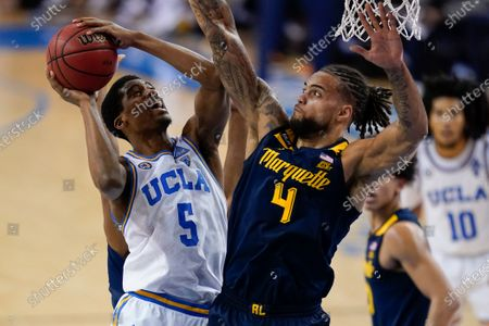 Guard Chris Smith (5) is defended by Marquette forward Theo John (4) during the second half of an NCAA college basketball game, in Los Angeles
