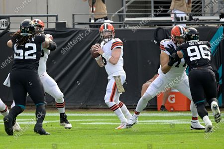 Stock Picture of Cleveland Browns quarterback Baker Mayfield (6) sets up to throw a pass between Jacksonville Jaguars defensive tackle DaVon Hamilton (52) and defensive end Adam Gotsis (96) during the first half of an NFL football game, in Jacksonville, Fla