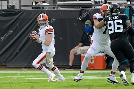 Cleveland Browns quarterback Baker Mayfield (6) sets up to throw a pass as offensive tackle Jedrick Wills Jr. (71) blocks against Jacksonville Jaguars defensive end Adam Gotsis (96) during the first half of an NFL football game, in Jacksonville, Fla