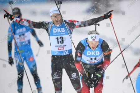 Stock Photo of Tarjei Boe of Norway (R) and Simon Eder of Austria (C) react in the finish area during the Men's 12.5km Pursuit race at the IBU Biathlon World Cup event in Hochfilzen, Austria, 12 December 2020.