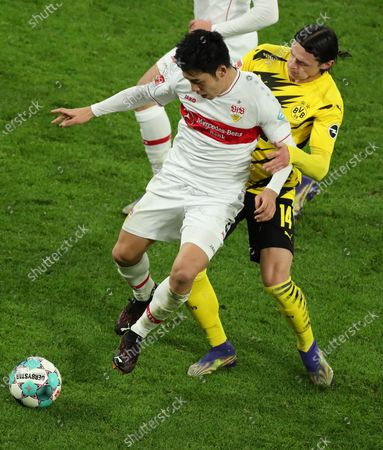 Stuttgart's Wataru Endo (L) in action against Dortmund's Nico Schulz (R) during the German Bundesliga soccer match between Borussia Dortmund and VfB Stuttgart in Dortmund, Germany, 12 December 2020.