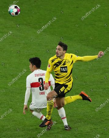 Stuttgart's Wataru Endo (L) in action against Dortmund's Mats Hummels (R) during the German Bundesliga soccer match between Borussia Dortmund and VfB Stuttgart in Dortmund, Germany, 12 December 2020.