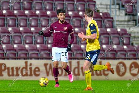 Josh Ginnelly (#30) of Heart of Midlothian FC runs at James Maxwell (#3) of Queen of the South FC during the SPFL Championship match between Heart of Midlothian and Queen of the South at Tynecastle Park, Edinburgh