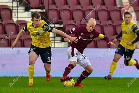 Steven Naismith (#14) of Heart of Midlothian FC turns away from James Maxwell (#3) of Queen of the South FC during the SPFL Championship match between Heart of Midlothian and Queen of the South at Tynecastle Park, Edinburgh