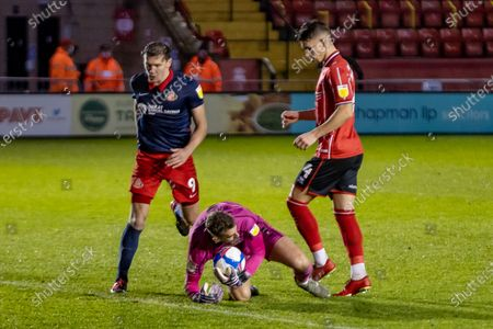 Lincoln City  Goalkeeper Alex Palmer (1) saves at the feet of Sunderland forward Charlie Wyke (9) during the EFL Sky Bet League 1 match between Lincoln City and Sunderland at Sincil Bank, Lincoln