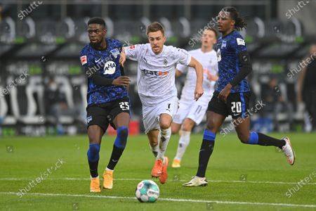 Moenchengladbach's Patrick Herrmann (C) in action against Hertha players Jordan Torunarigha (L) and Dedryck Boyata (R) during the German Bundesliga soccer match between Borussia Moenchengladbach and Hertha BSC Berlin in Moenchengladbach, Germany, 12 December 2020.