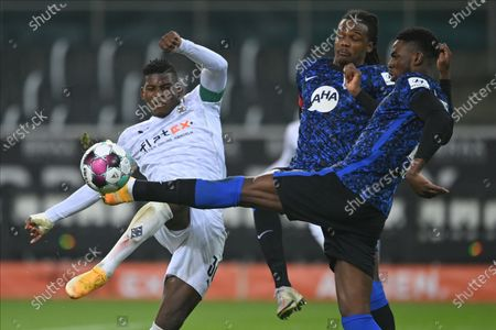 Moenchengladbach's Breel Embolo (L) in action against Hertha players Dedryck Boyata (C) and Jordan Torunarigha (R) during the German Bundesliga soccer match between Borussia Moenchengladbach and Hertha BSC Berlin in Moenchengladbach, Germany, 12 December 2020.