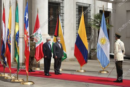 The President of Chile, Sebastian Pinera (L), receives with military honors the president of Colombia, Ivan Duque (C), at the Palacio de La Moneda, in Santiago, Chile, 12 December 2020. Pinera, who received Duque, the previous day to head the 15th Summit of the Pacific Alliance, handed over the pro tempore presidency of the Forum for the Progress of South America (Prosur), to the Colombian president on 2020.