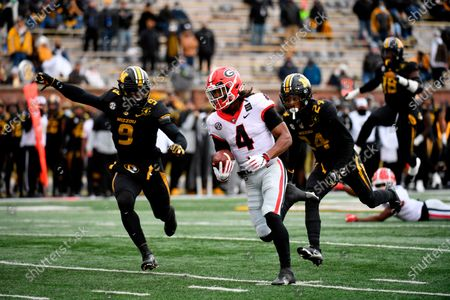 Stock Photo of Georgia running back James Cook (4) runs past Missouri defensive back Ishmael Burdine (24) and safety Tyree Gillespie (9) on his way to a touchdown during the first half of an NCAA college football game, in Columbia, Mo