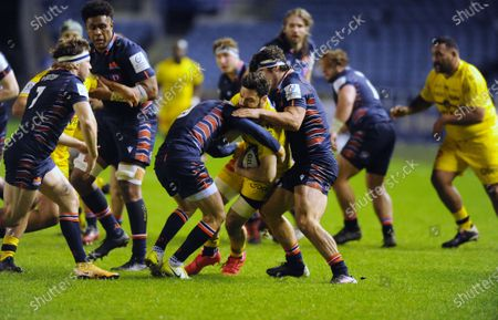 Kevin Gourdon - La Rochelle flanker tackled by Henry Pyrgos and Stuart McInally (R).