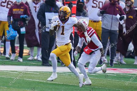 Minnesota running back Cam Wiley (1) is chased by Nebraska safety Deontai Williams (8) during the first half of an NCAA college football game in Lincoln, Neb