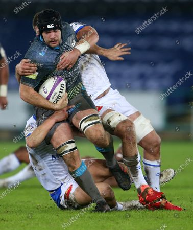 Morgan Morris of Ospreys is tackled by Thomas Fortunel and Kevin Kornath of Castres.