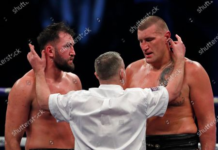 Poland's Mariusz Wach, right, and Britain's Hughie Fury are spoken to by the referee during the Heavyweight boxing fight at Wembley Arena in London