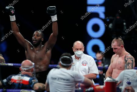 Britain's Lawrence Okolie, left, celebrates after beating Poland's Nikodem Jezewski in a Cruiserweight boxing fight at Wembley Arena in London