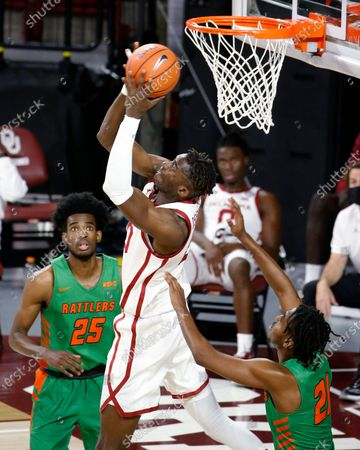Oklahoma's Rick Issanza (20) goes up against Florida A&M's Johnny Brown (21) and DJ Jones (25) during the second half of an NCAA college basketball game in Norman, Okla