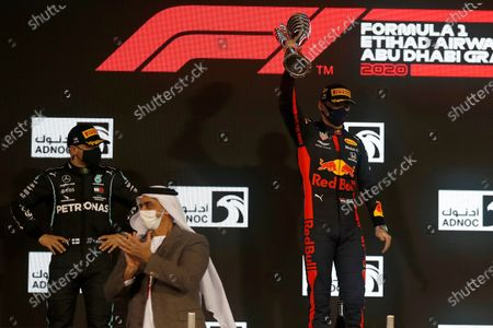 Red Bull driver Max Verstappen of the Netherlands celebrates wining as Mercedes driver Valtteri Bottas of Finland,left, looks on after the Formula One at the Yas Marina racetrack in Abu Dhabi, United Arab Emirates, Sunday, Dec.13, 2020