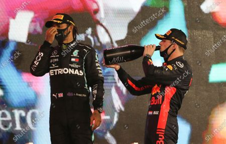 Mercedes driver Lewis Hamilton of Britain, left, and Red Bull driver Max Verstappen of the Netherlands stand on the winners podium after the Formula One Abu Dhabi Grand Prix in Abu Dhabi, United Arab Emirates