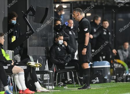 Referee Andre Marriner looks at a replay of the video assistant referee (VAR) during the English Premier League soccer match between Fulham FC and Liverpool FC in London, Britain, 13 December 2020.