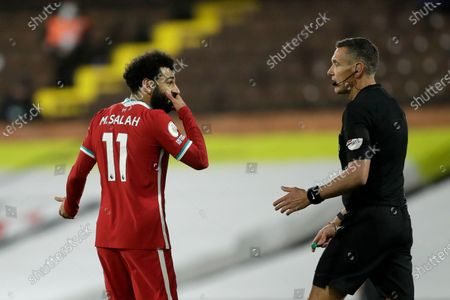 Liverpool's Mohamed Salah talks to Referee Andre Marriner during the English Premier League soccer match between Fulham and Liverpool, at Craven Cottage stadium, London
