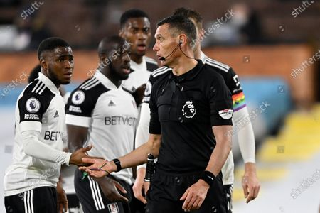 Fulham players react after Referee Andre Marriner awarded Liverpool a penalty shot during the English Premier League soccer match between Fulham and Liverpool, at Craven Cottage stadium, London