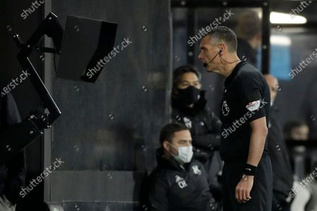 Referee Andre Marriner watches a replay to check for a possible penalty during the English Premier League soccer match between Fulham and Liverpool, at Craven Cottage stadium, London