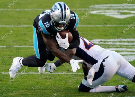 Stock Photo of Carolina Panthers wide receiver Curtis Samuel is tackled by Denver Broncos safety Kareem Jackson during the second half of an NFL football game, in Charlotte, N.C