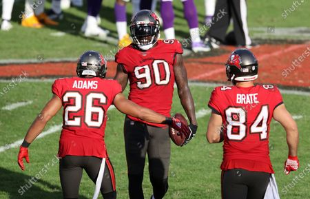 Tampa Bay Buccaneers outside linebacker Jason Pierre-Paul (90) celebrates with defensive back Andrew Adams (26) and tight end Cameron Brate (84) during the second half of an NFL football game against the Minnesota Vikings, in Tampa, Fla