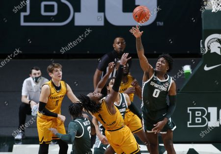 Michigan State's Aaron Henry, right, blocks a shot by Oakland's Rashad Williams (1) as Oakland's Blake Lampman, left, and Michigan State's Rocket Watts (2) and Malik Hall, rear, watch during the first half of an NCAA college basketball game, in East Lansing, Mich