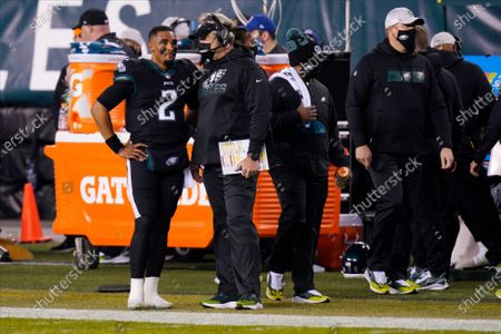 Philadelphia Eagles' Jalen Hurts left, and Doug Pederson talk during the first half of an NFL football game against the New Orleans Saints, in Philadelphia